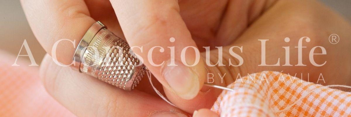 dedos con dedal cosiendo. coser